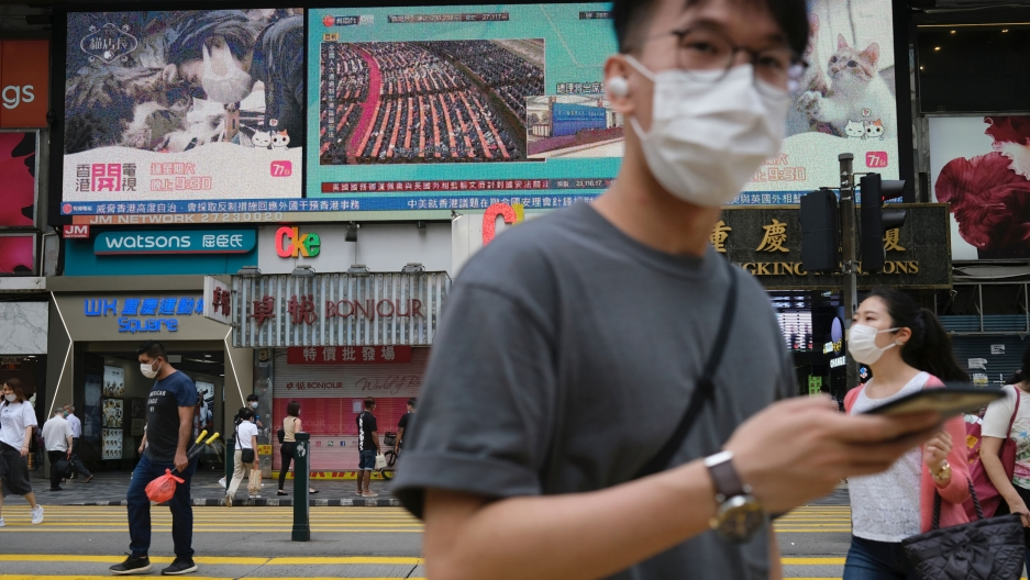 People walk past a TV screen showing news of Beijing's approval of a controversial Hong Kong security bill, in Hong Kong, May 28, 2020.