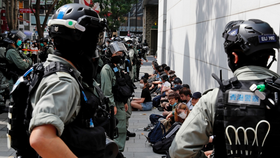 A line of young demonstrators are shown sitting on the ground next to a building with riot police standing in front of them.