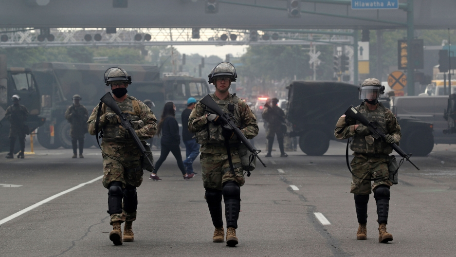 Several US National Guard members are shown wearing military fatigues and carrying weapons while walking in a street.