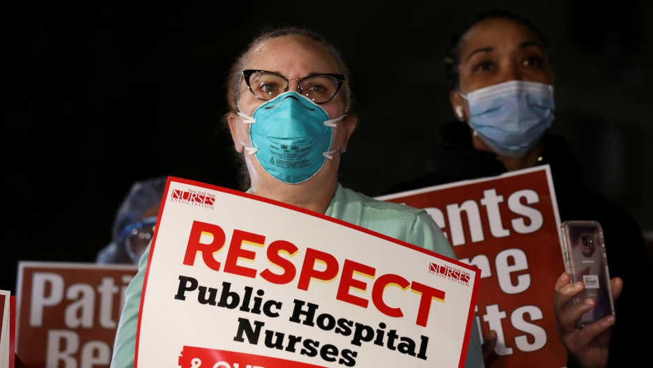 Two women stand with protest signs about respecting nurses