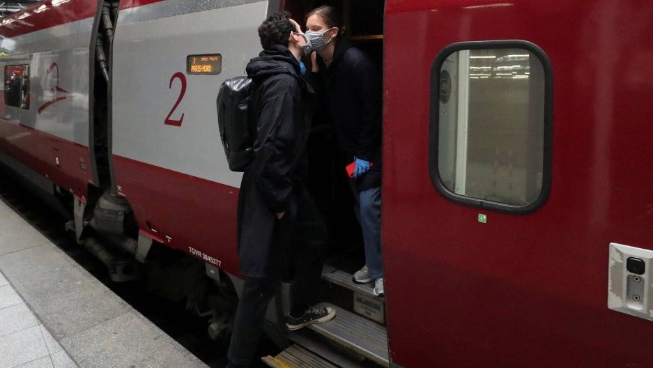 Two people kiss wearing face masks as they board a train