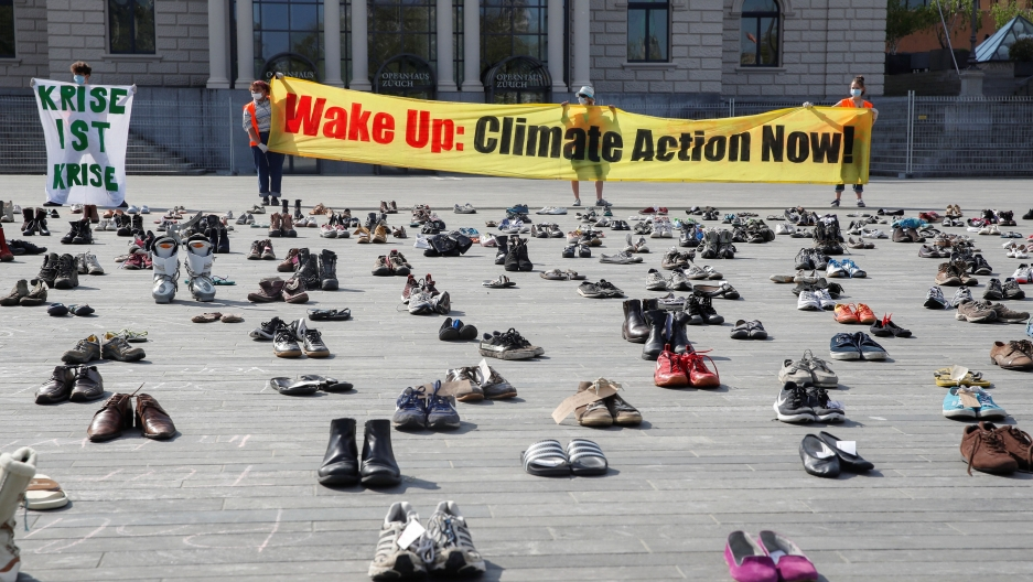 Environmental activists of Swiss Klimastreik Schweiz movement hold banners, as the spread of the coronavirus disease (COVID-19) continues, in front of the opera house on the Sechselaeutenplatz square in Zurich, Switzerland, April 24, 2020.