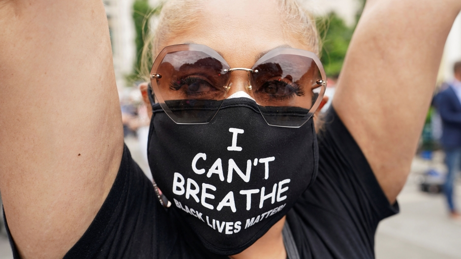 "A close of a woman with a face mask reading ""I can't breathe Black Lives Matter"""