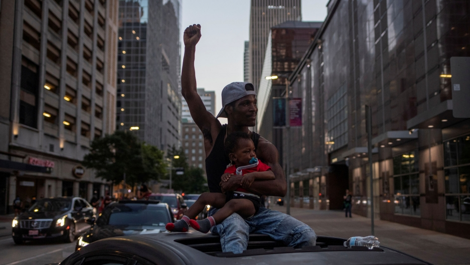 A man is shown sitting on the roof of his car through the sunroof and hold a young child in his lap while raising his fist.