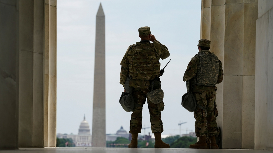 Two US soldiers are shown looking out at the Washington Monument with the US Capitol Building off in the distance.