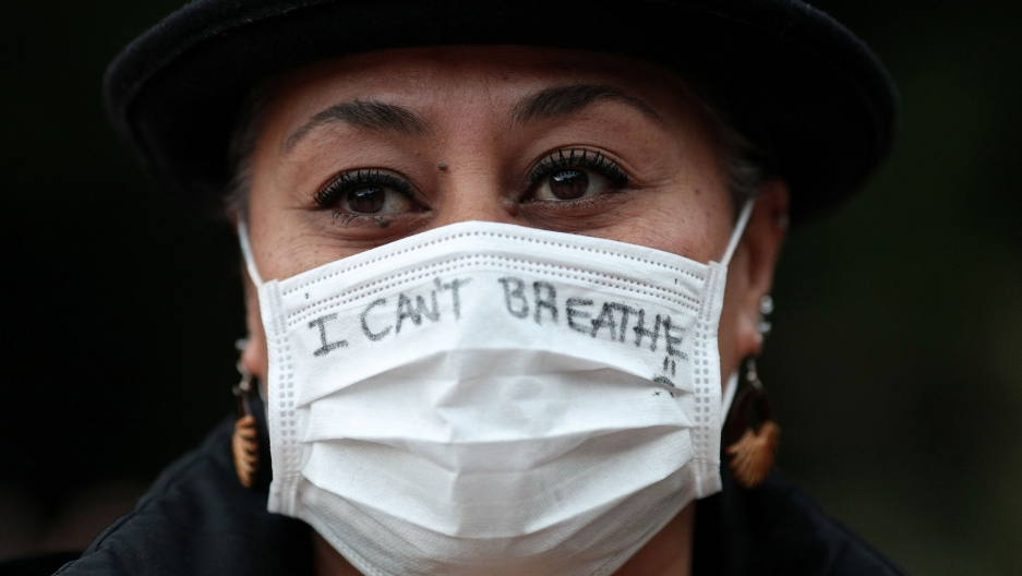 "A close up photograph of a woman wearing a white protective face mask with the words, ""I can't breathe"" written on it."