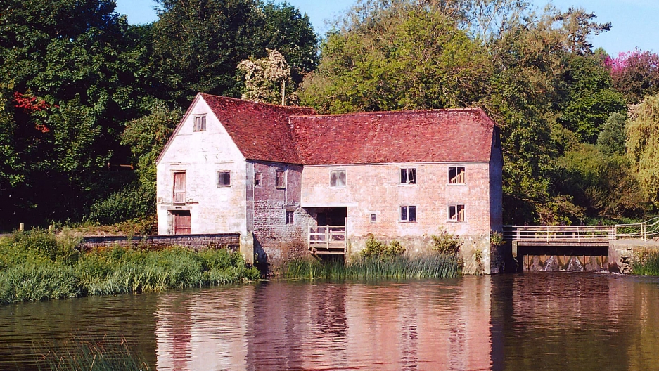 The Sturminster Newton Mill brick and stone building is shown across a body of water with its refection in the water.