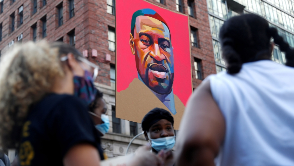 A portrait of George Floyd is seen hanging in the background as demonstrators in the near ground are in soft focus.