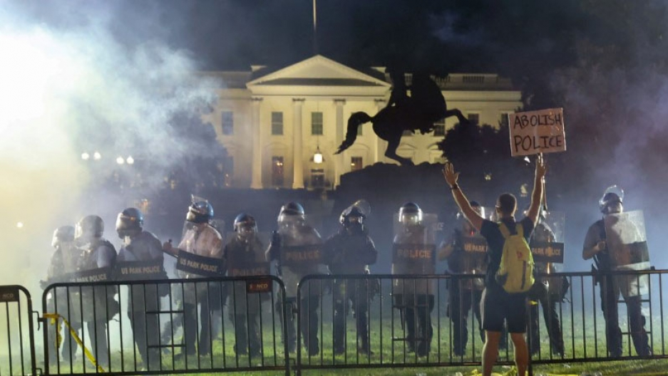 Smoke in front of the White House as riot police stand with a protester in the foreground.