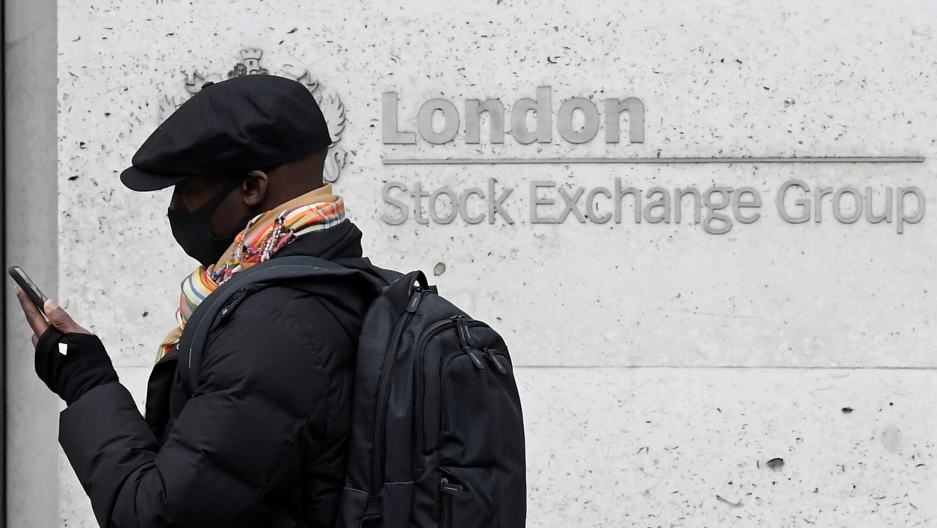 A man wearing a protective face mask and hat walks past the London Stock Exchange Group building