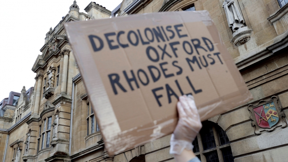 "A demonstrator's hand is seen holding a placard reading ""Decolonise Oxford/Rhodes must fall"""