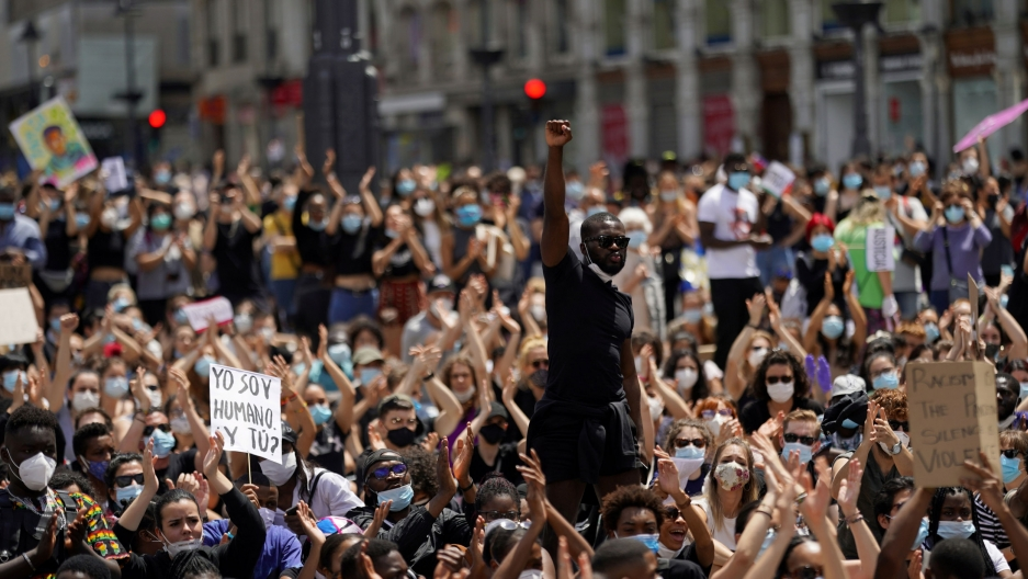 A large group of people are shown in a crowd with man in the middle raising his right fist in the air.