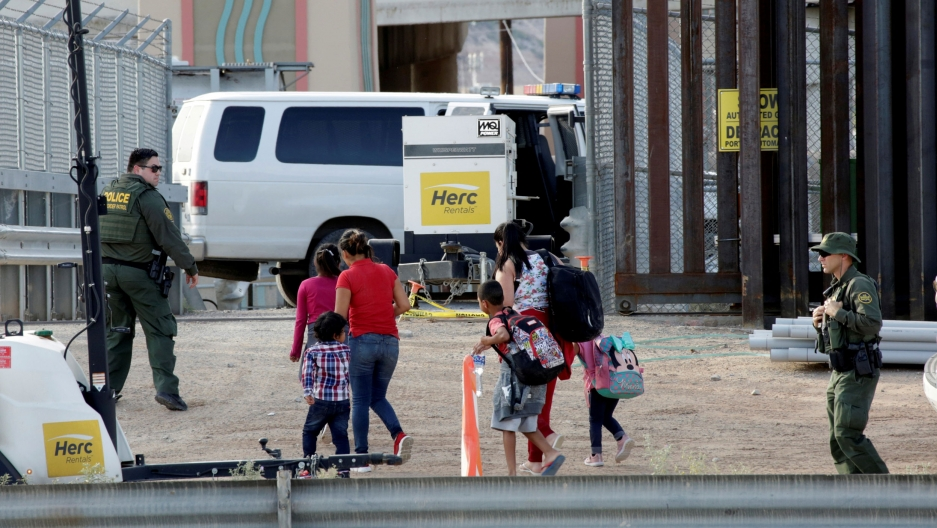 US Customs and Border Protection (CBP) agents look at women and children