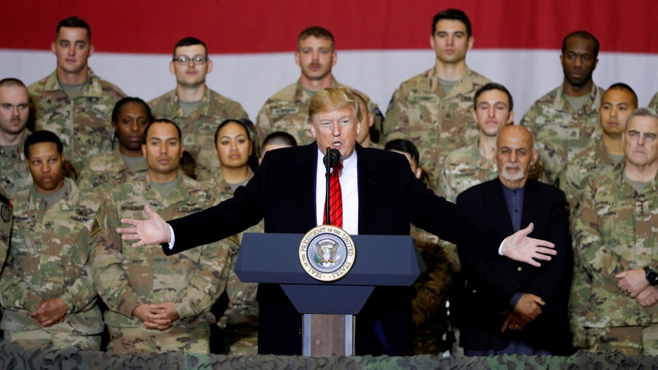 US President Donald Trump is shown standing at a podium with his arms outstretched and rows of US soldiers wearing fatigues standing behind him.