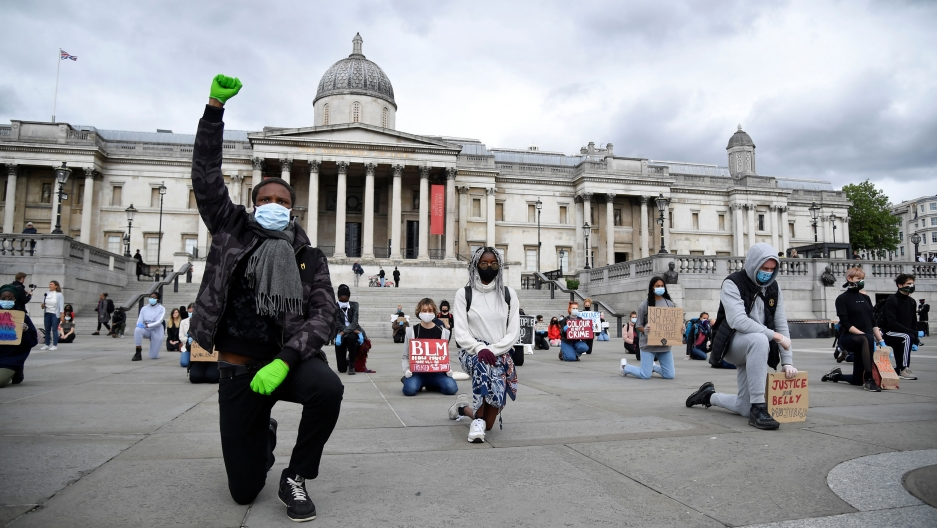 A large group of people are shown kneeling while spaced apart from each other in Trafalgar Square.