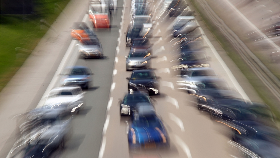 A three lane highway is shown packed with cars and taken with a blurry effect.