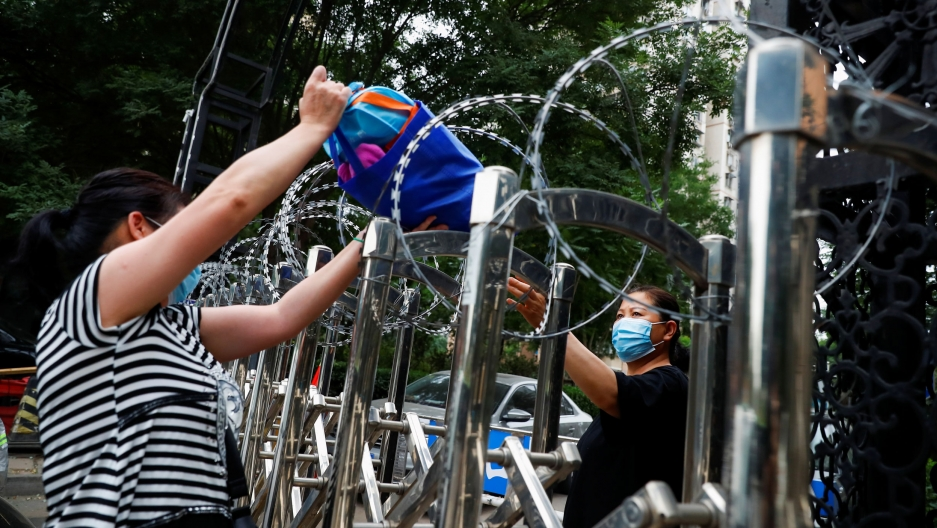 A person is shown passing a bag over a metal fence that has barbed wire on top.