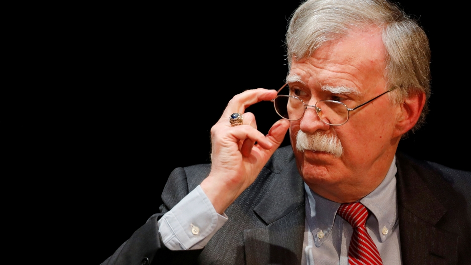 Former US national security advisor John Bolton is shown wearing a stripped suit and red tie and adjusting his glasses.