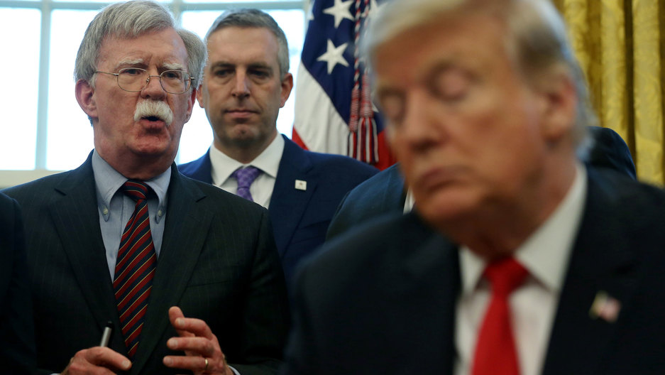 John Bolton is shown speaking in distance with US President Donald Trump in the nearground in soft focus.