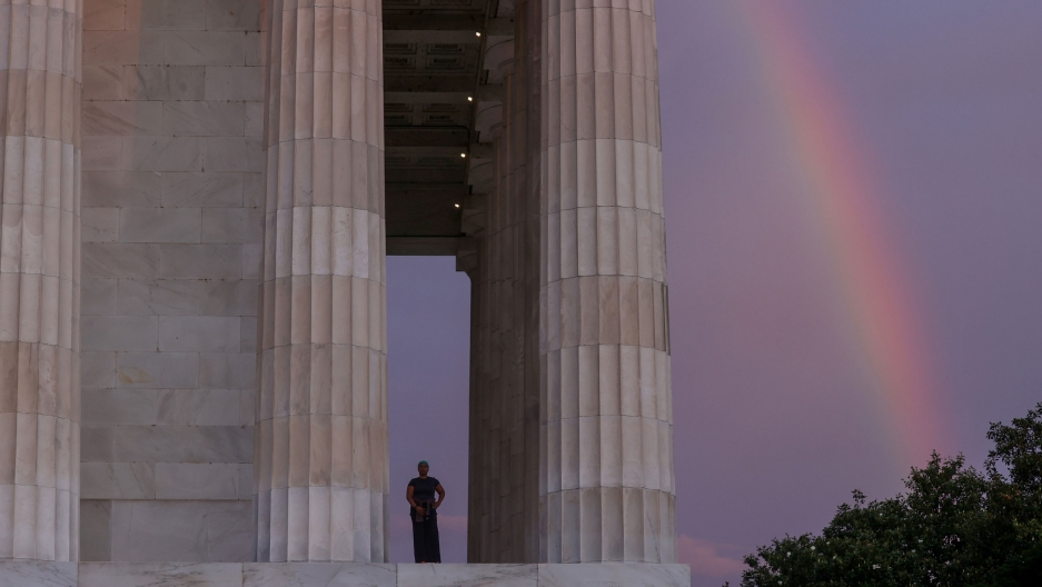 A side view of the Lincoln Memorial shows a woman standing near the large pillars and a rainbow in the distance.