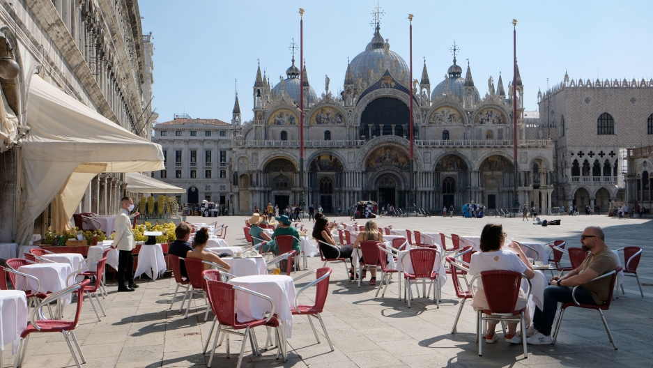 Several cafe tables are shown in St. Mark's Square with the St. Mark's Basilica in the distance.