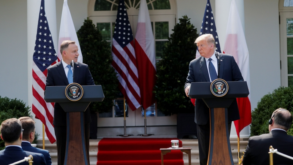 US President Donald Trump and Poland's President Andrzej Duda are shown standing at podiums across from each other with the White House in the background.