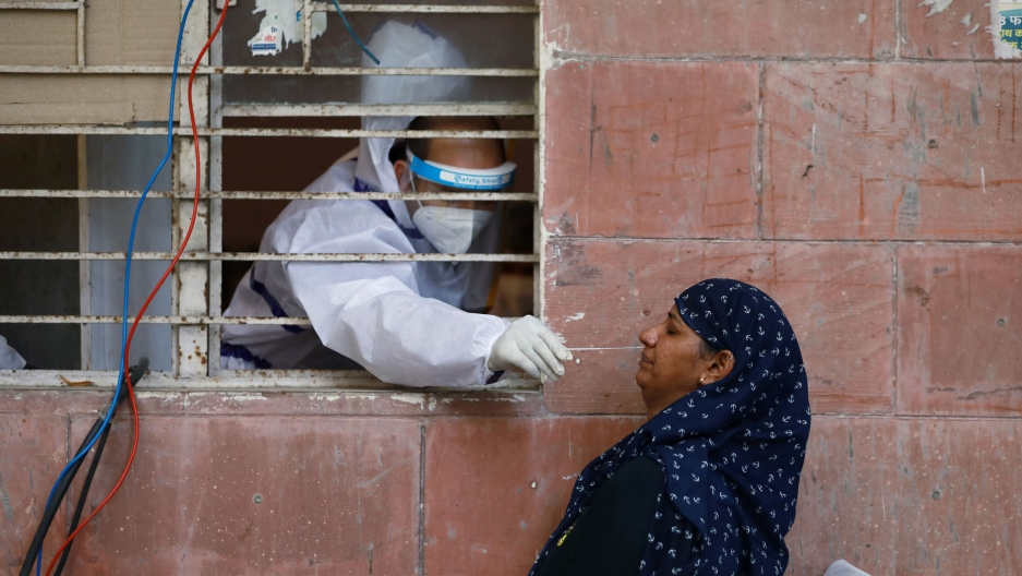 A medical worker is shown reaching through a window with bars on it while wearing protective medical gear and a women outside being tested for the coronavirus.