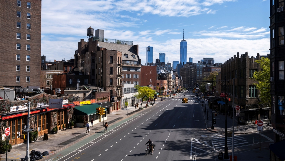 A cyclist is shown rides up a nearly empty three lanes of 7th Avenue with the Freedom Tower in the distance.