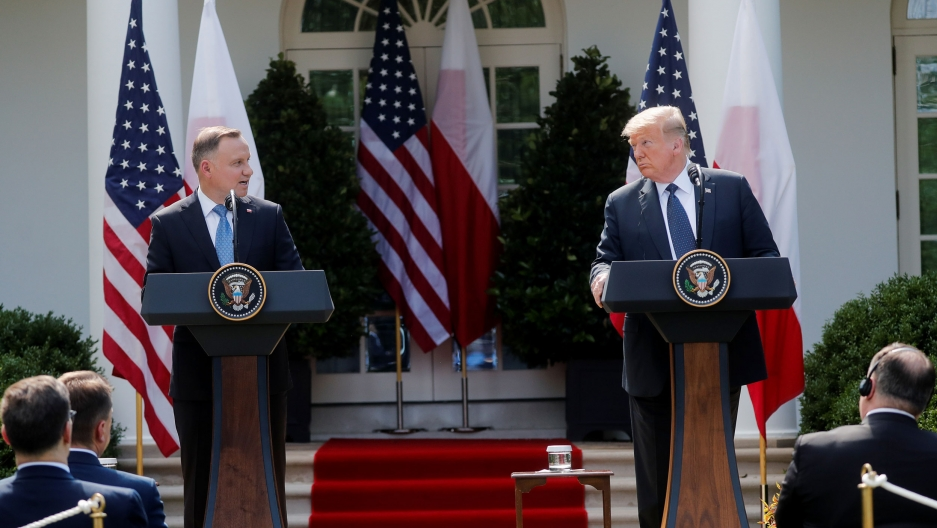 Two white men in suits stand at podiums in front of the US and Polish flags