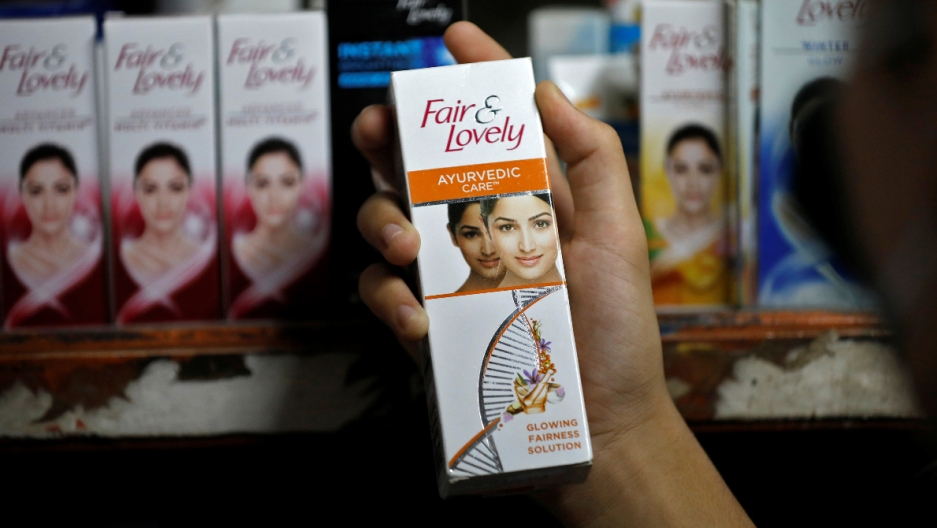 Skin lightening creams are exhibited on a shelve while a holds one cream in her hand.