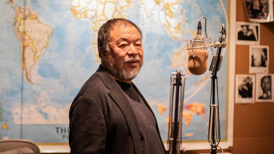 Ai Weiwei looks at the camera as he stands in front of a microphone