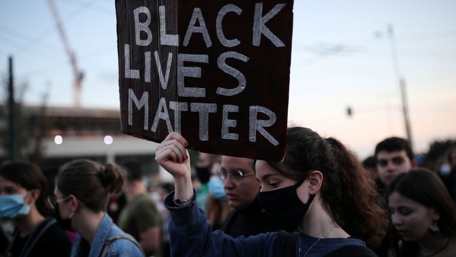 "A large group of people are shown in a crowd with one woman in the center carrying a sign with ""Black Lives Matter"" written on it."