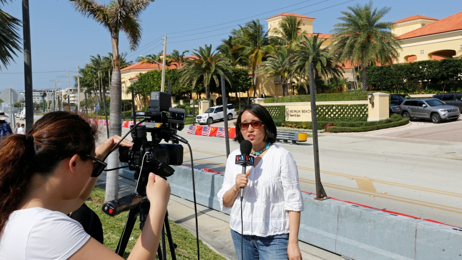 A woman reporters with a camera crew outside near palm trees.