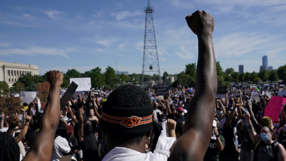A black man stands in a crowd with his fist raised in the air.