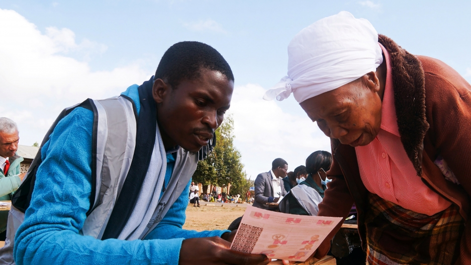 A man in Malawi wearing a blue shirt explains a document to an elderly woman wearing a white head wrap outside