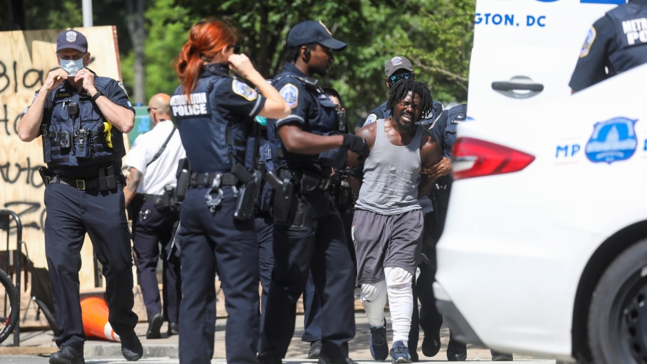 A group of police officers in black uniforms detain a Black man wearing gray pants and white tank.