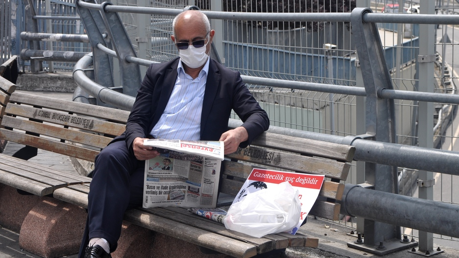 A man in a suit reads a newspaper on a bench outside