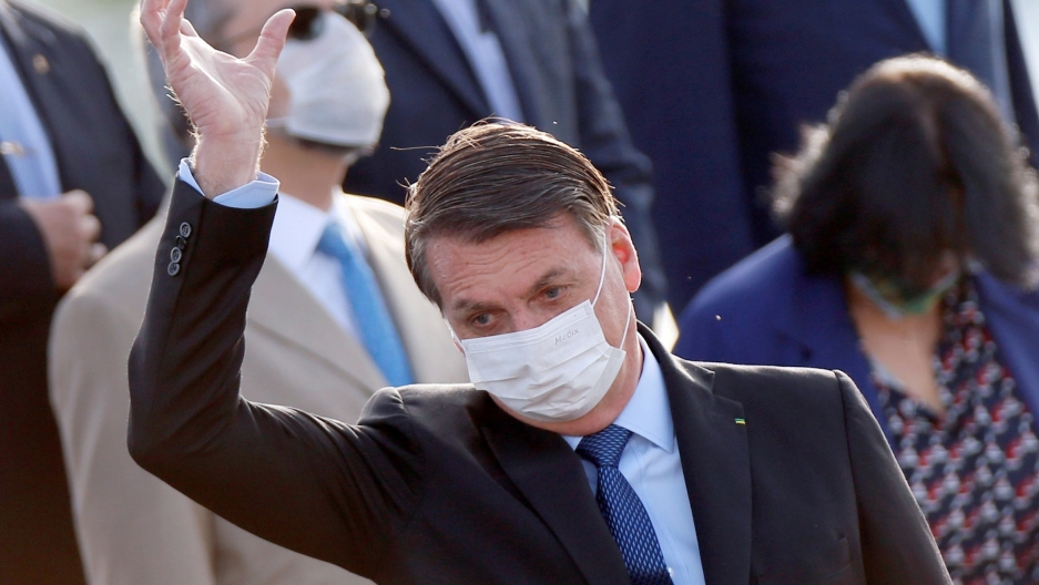 Brazil's President Jair Bolsonaro wearing a protective face mask gestures during a national flag hoisting ceremony in front of Alvorada Palace, amid the coronavirus disease (COVID-19) outbreak in Brasilia, Brazil, June 9, 2020.
