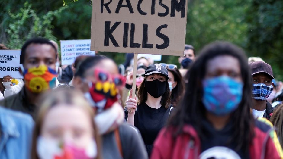 "Protesters march. One sign reads ""Racism Kills."""