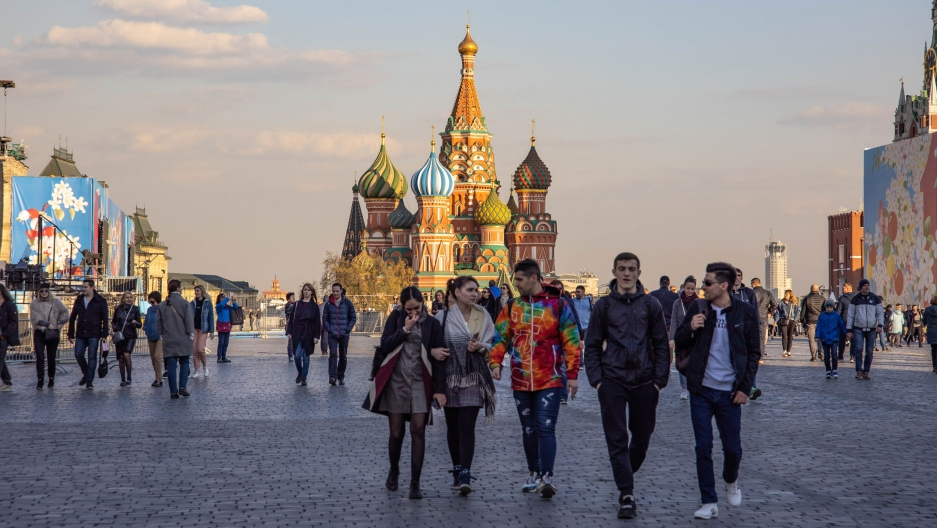 People walk through Red Square in Moscow. St. Basil's Cathedral is in the distance.