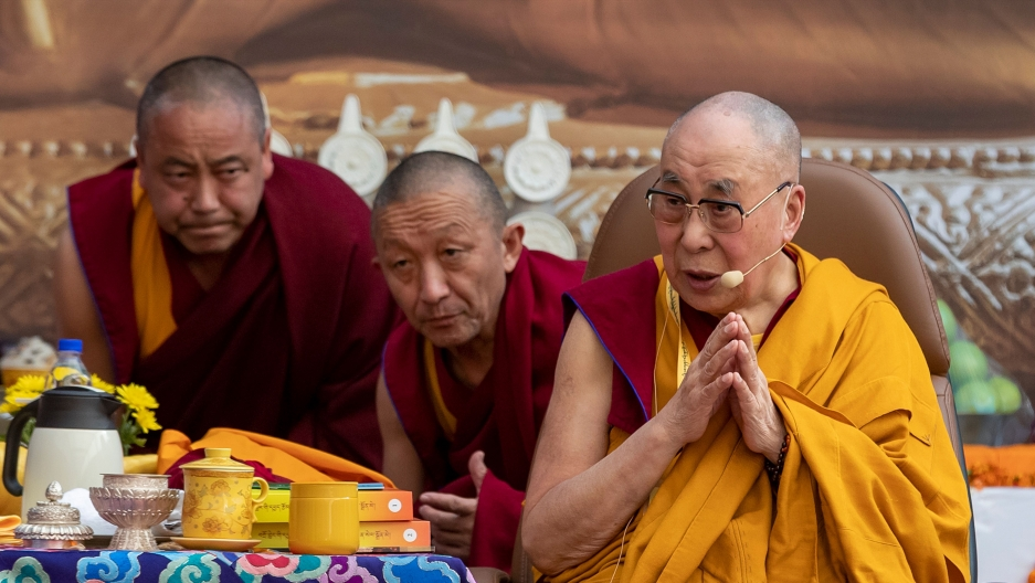 The Dalai Lama speaks while wearing a yellow robe. He is surrounded by two man on red robes in a monastery.