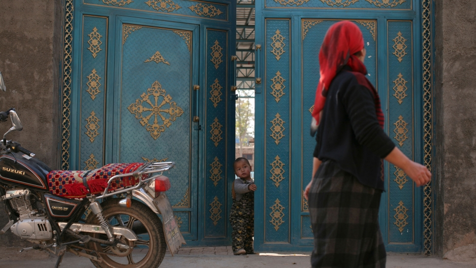 A child looks out from a door as a Uighur woman walks by