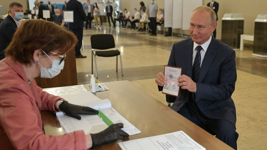 Putin holds his passport in front of an election official
