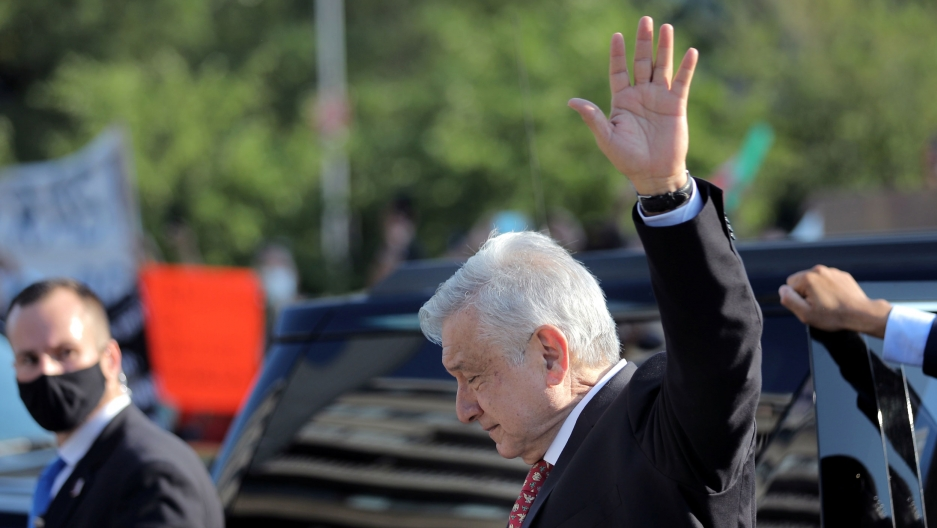 Mexico's President Andrés Manuel López Obrador is shown from the side wearing a dark suit and waving his left hand in the air.