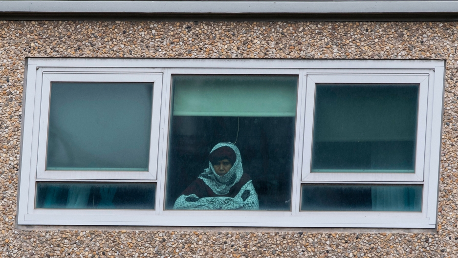 A woman is shown from looking through a window and wearing a shirt with a hood over her head.