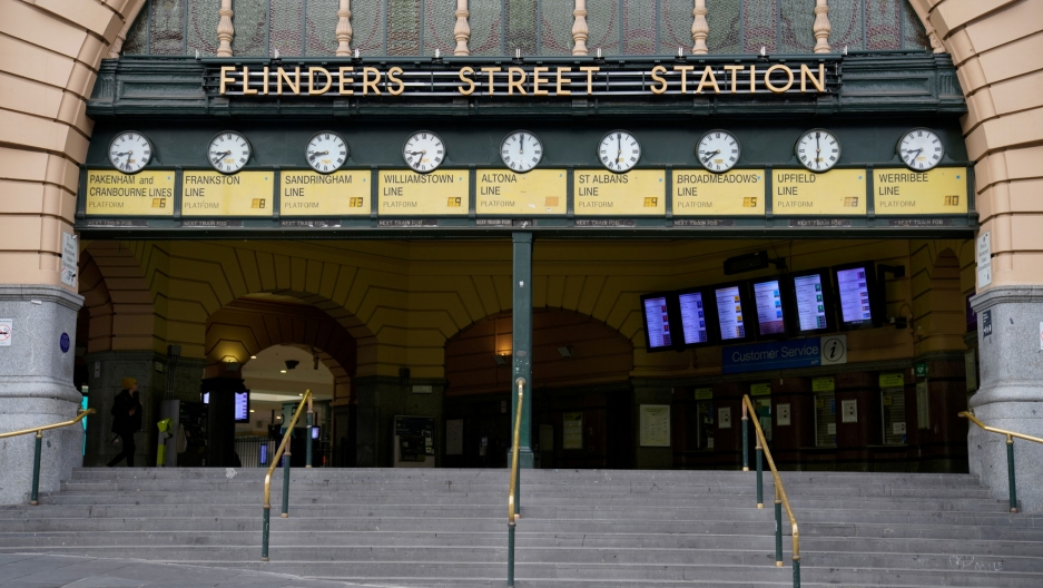 The entrance to Flinders Street train station is shown with nine clocks along the top and nearly empty of people.