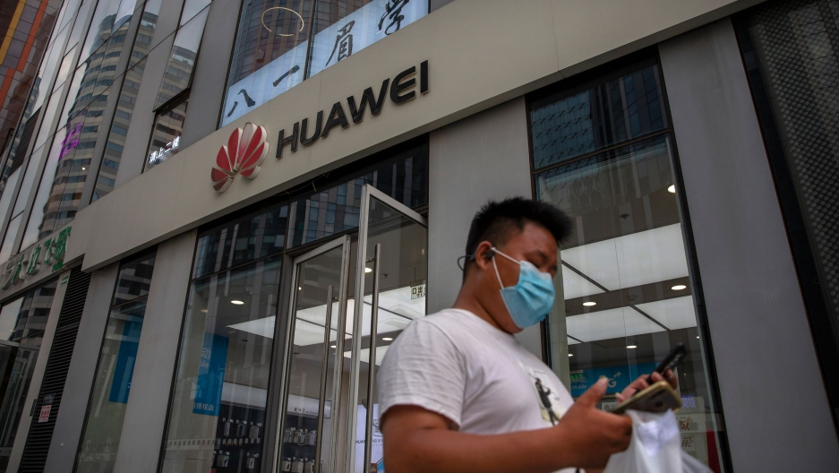 A man is shown looking down at this phone and wearing a face mask with a Huawei store in the background.