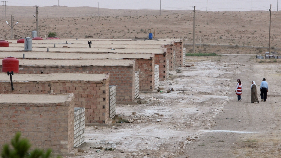 A row of brick shelters are shown amidst a sandy desert location with three people walking in the distance.