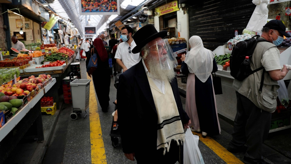 People wear face masks as they shop in a main market in Jerusalem, Israel, July 16, 2020.