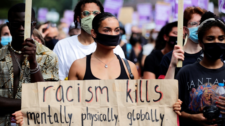 A large crowd of people are shown with a women featured in the center of the photograph holding a sign that reads, racism kills, mentally. physically. globally.